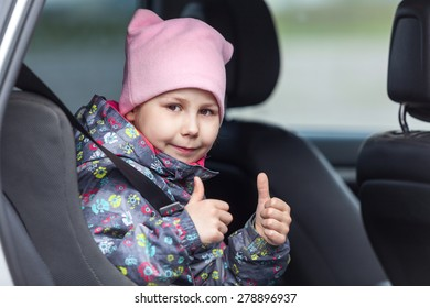 Little child is in the booster chair fastening with car seatbelt, thumbs up showing