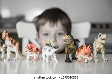 Little child boy is afraid of dinosaurs. Phobia, fear and horror concept