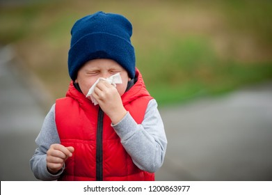 Little child boy blow his nose. Sick child with napkin in autumn park. Allergic kid, flu season. Kid with cold rhinitis, get cold