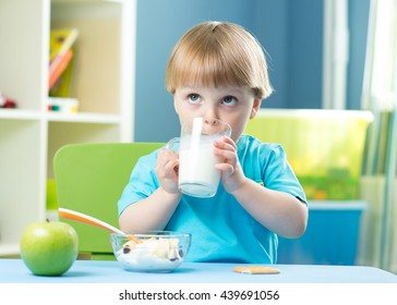 Little child boy holding glass of milk