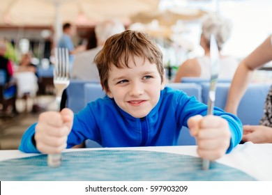 Little child boy hungry waiting for dinner in restaurant. Holding fork and knife