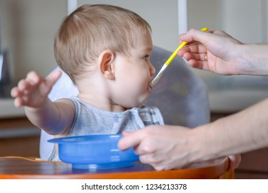 Little child boy learns to eat at the children's table in the kitchen. Mom feeds holding out her hand with a spoonful of porridge
