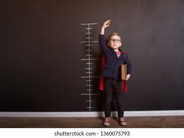 Little child boy measuring growth near blackboard wall. Happy smiling kid in glasses ready for education. Success, motivation concept. Back to school. Little businessman, Boy superhero.