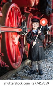 Little child boy as nostalgic railroad conductor with cap and signaling disk beside large wheels of a steam locomotive/Little Train Conductor Boy