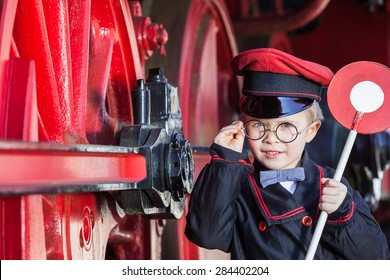 Little child boy as nostalgic railroad conductor with cap and signaling disk beside large wheels of a steam locomotive/Smiling Train Conductor Boy