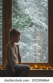 little child boy sitting by window looking outside pensive concentrated. indoors lifestyle portrait of kid  dreaming on wooden windowsill close up winter weather.