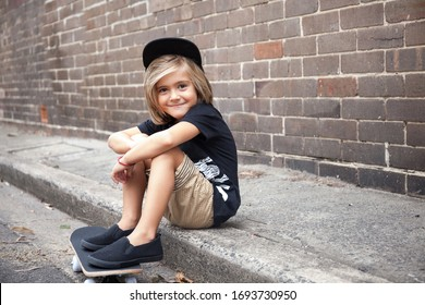 Little child boy sitting on a skateboard sitting on a pathway, cool street style outfit