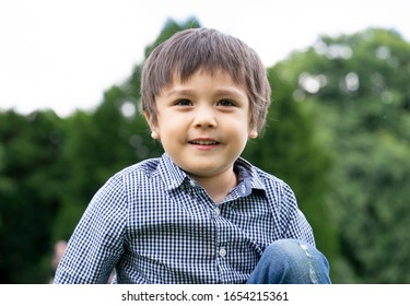 Little Child boy with smiling face sitting in the park with blurry  natural bokeh background, Portrait  of happy kid playing outdoors in spring or summer.