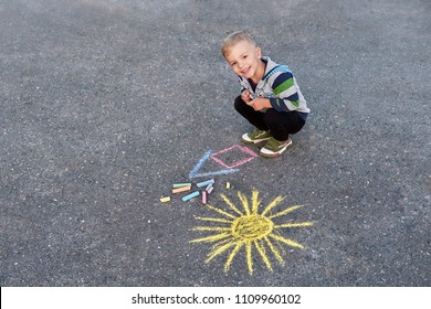 Little child boy smiling siting on asphalt sidewalk,drawing house, sun painted by colored chalk.Children's picture,creativity on gray dackground road. Kid looking camera, top view,copy space.