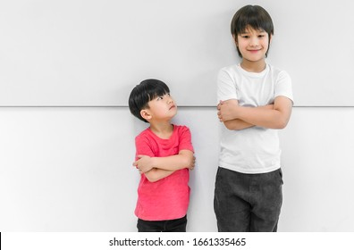Little child boy standing arms crossed and looking face of tall child at standing arms crossed and smiling. Big and small kid concept at be friends.