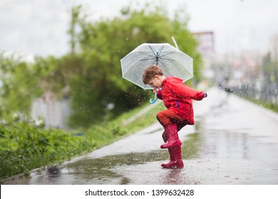 little child boy with an umbrella playing out in the rain in the summer outdoors