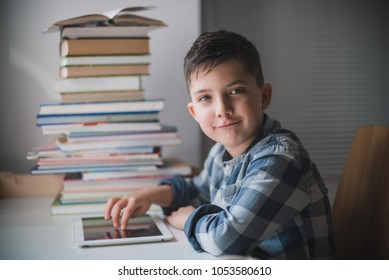 Little child boy is using a tablet and sitting at a table in the background of a pile of books.