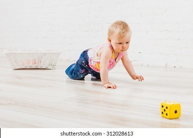 Little child crawling to cubes on light wooden floor; cute baby girl crawling; happy baby  playing on floor