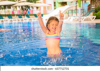 A little child is dancing in the pool. Beach party, summer vacation.