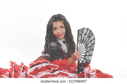 Little child dancing spanish dance. Small girl sitting in red costume