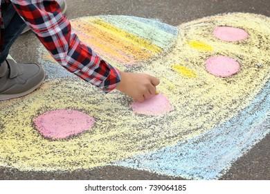 Little child drawing alien spaceship with chalk on asphalt, closeup
