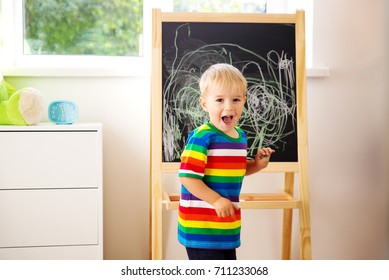 Little child drawing on the blackboard. Boy standing in the room with chalkboard