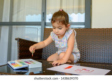 Little child drawing a picture with paint and brush. Cute little brunette girl sitting among comfortable modern design garden furniture with couch, armchairs, and table arranged on a home patio.