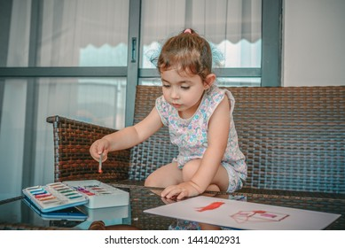 Little child drawing a picture with paint and brush. Cute little brunette girl sitting among comfortable modern design garden furniture with couch, armchairs, and table arranged on a home terrace.