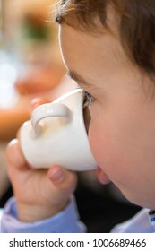 Little child drinks from mug