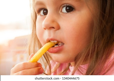 Little child eating a french fries in the cafe
