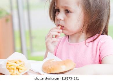 Little child eating a hamburger on the street