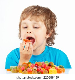 Little child eating jelly candies on a white background