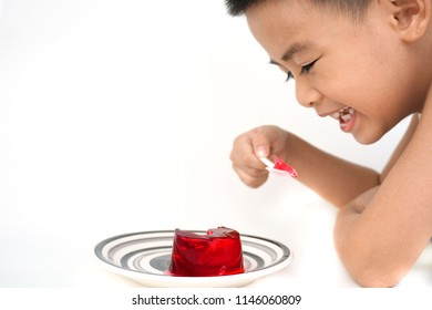 Little child eating jelly on white background