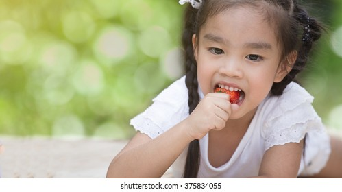 little child eating strawberries
