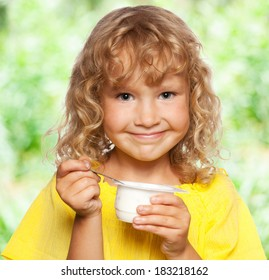 Little child eating yogurt outdoors