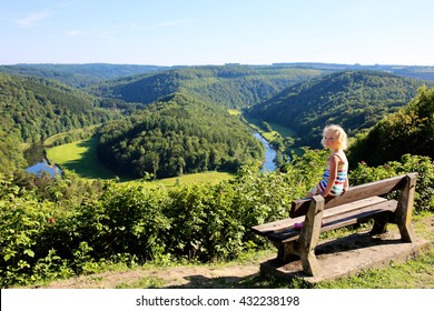 Little child enjoying elevated view from famous panoramic viewpoint of The Giant's tomb lying inside the bend of the river Semois, located nearby the city of Bouillon, Wallonia, Ardennes, Belgium.