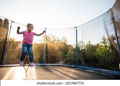 Little child enjoying as she jumps on trampoline bed