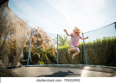 Little child enjoys jumping on trampoline - outside in backyard