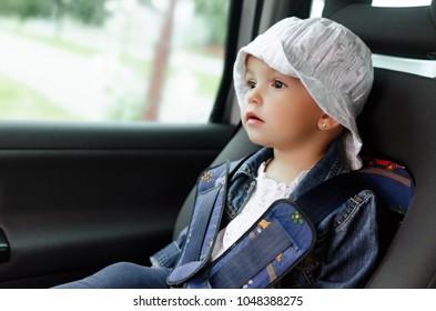 Little child fasten seat belt in high back booster car seat. Child safety.