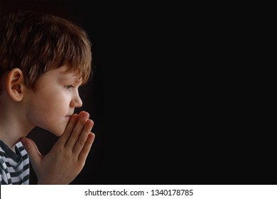 Little child folded his hand with praying in black background. Religion, prayer, faith and spirituality concept.
