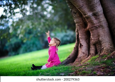 Little child in the forest with a huge trees and green grass
