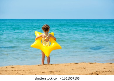 A little child girl 3 years old stands with a yellow swimming ring in the form of a starfish and looks at the sea. Back view