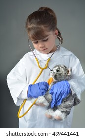 Little child (girl age 6) who wants to be a veterinarian play pretend to be an animal doctor in veterinary clinic. Medical concept with copy space
