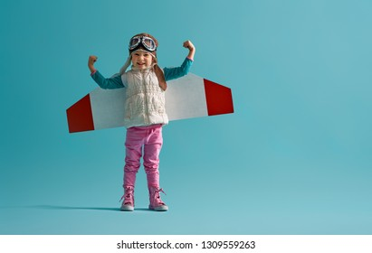 Little child girl in an astronaut costume is playing and dreaming of becoming a spaceman. Portrait of funny kid on a background of bright blue wall.