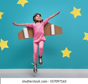 Little child girl in an astronaut costume is playing and dreaming of becoming a spaceman. Portrait of funny kid on a background of bright blue wall with yellow stars.