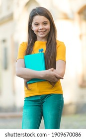 Little child girl back to school hold textbook, learning is fun concept.