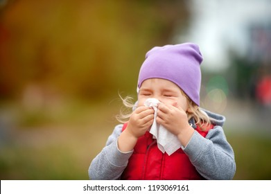 Little child girl blow her nose. Sick child with napkin in autumn park. Allergic kid, flu season. Kid with cold rhinitis, get cold