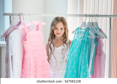 Little child girl choosing her clothes. Kid thinking what to choose to wear in front of many choices of dresses on hangers. Sales, buy and sell concepts.
