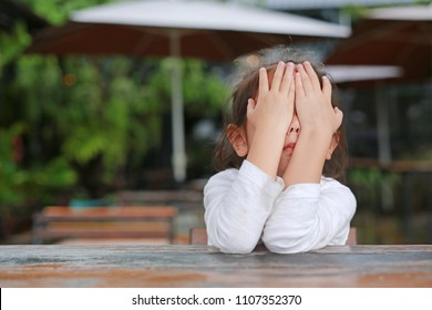 Little child girl closes her eyes with hands on wooden table.