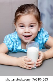 Little child girl drinking a milk at kitchen