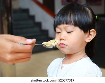 Little child girl eating boring food. Kid girl bored with food.
