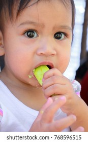 little child girl are eating cucumber by herself