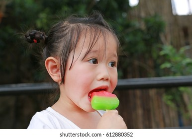 Little child girl eating ice-cream in the park