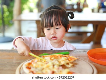 Little child girl enjoy eating pizza.