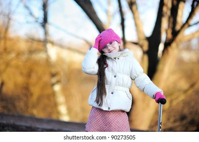 Little child girl in glasses wearing pink cap with a scooter